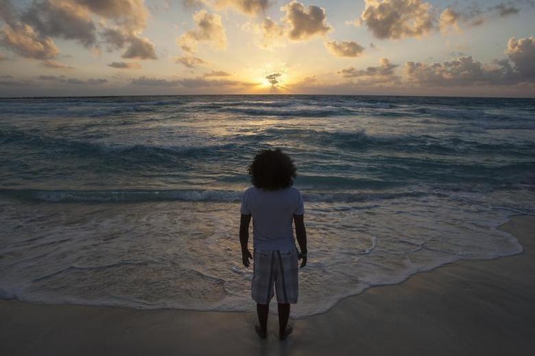 A man watches the sunrise on New Year's Day at Gaviota Azul beach in Cancun January 1, 2014. REUTERS/Victor Ruiz Garcia