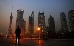 Um homem olha na direção do distrito financeiro de Pudong, em Xangai. A China aprovou um plano piloto que permite a criação de três a cinco bancos privados, disse a agência reguladora nesta segunda-feira, em um passo para fortalecer o apoio financeiro para empresas menores e famintas por recursos. 20/11/2013 REUTERS/Carlos Barria
