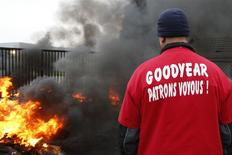 An employee of U.S. tyre-maker Goodyear stands in front of burning tires at the entrance of the plant in Amiens, northern France, to protest job cuts and the project to close the French plant in Amiens in this November 18, 2013 file picture. REUTERS/Benoit Tessier/Files