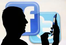 A man is silhouetted as he uses a mini tablet computer while standing in front of a video screen with the Facebook and Twitter logos, in this picture illustration taken in Sarajevo October 22, 2013. REUTERS/Dado Ruvic