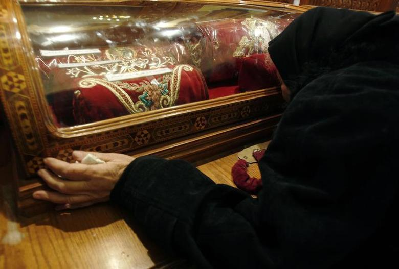 Trieza ,73, an Egyptian Christian grieves while kissing a glass capsule containing cloth belonging to Christian martyrs in the Coptic Orthodox church in Alexandria, 2, 2011. REUTERS/Amr Abdallah Dalsh