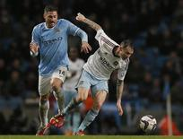Manchester City's Javi Garcia (L) challenges West Ham United's Matt Taylor during their English League Cup semi-final first leg soccer match at the Etihad Stadium in Manchester, northern England January 8, 2014. REUTERS/Phil Noble