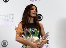 """Atriz Sandra Bullock posa para foto com os troféus recebidos no Prêmio People's Choice 2014, em Los Angeles. Sandra Bullock dominou a 40ª edição do People's Choice (""""escolha popular""""), com quatro troféus, consolidando-se como favorita nos prêmios com votação do público, enquanto o cantor Justin Timberlake dominou as categorias musicais, com três prêmios. 8/01/2014. REUTERS/Kevork Djansezian"""