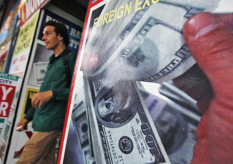 A tourist leaves a currency exchange shop at a shopping arcade in New Delhi August 20, 2013. REUTERS/Anindito Mukherjee/Files