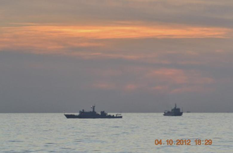 A handout photo shows two Chinese surveillance ships which sailed between a Philippines warship and eight Chinese fishing boats to prevent the arrest of any fishermen in the Scarborough Shoal, a small group of rocky formations whose sovereignty is contested by the Philippines and China, in the South China Sea, about 124 nautical miles off the main island of Luzon April 10, 2012. REUTERS/Philippine Army Handout