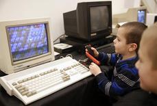 """Garoto joga jogo eletrônico no Commodore PC durante exposição """"História dos Computadores"""" em Sarajevo, 30 de novembro de 2013. As vendas globais de computadores pessoais (PCs) no mundo caíram 10 por cento no ano passado para 314,6 milhões de unidades, à medida que as fabricantes não conseguiram impedir que os consumidores optassem por smartphones e tablets, segundo dados preliminares da empresa de pesquisa IDC. 30/11/2013 REUTERS/Dado Ruvic"""