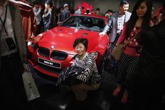 Uma mulher posa para uma foto próxima a um BMW M3 durante a 15ª Feira da Indústria Automotiva Internacional de Xangai, em Xangai. As vendas da montadora alemã de carros de luxo BMW na China cresceram 20 por cento em 2013, superando os Estados Unidos como o maior mercado do grupo. 21/04/2013 REUTERS/Carlos Barria