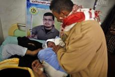 Palestinian baby boy Al-Hassan, the son of Palestinian prisoner Tamer al-Za'an (pictured in poster), who was conceived with al-Za'anin's sperm smuggled out of an Israeli prison, is held by al-Za'an's brother as his mother Hana rests on a bed at a hospital in Gaza City January 10, 2014. REUTERS/Suhaib Salem
