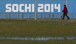 People walk past a banner near venues in the Olympic Park in Adler near Sochi, December 31, 2013. REUTERS/Maxim Shemetov
