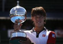 Kei Nishikori of Japan holds the trophy after winning the final against Tomas Berdych of the Czech Republic at the Kooyong Classic tennis tournament in Melbourne January 11, 2014. REUTERS/David Gray