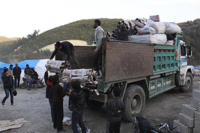 Syrian refugees receive aid in the al-Yamdiyeh refugee camp near the Syrian-Turkish border in Latakia province January 10, 2014. REUTERS/Khattab Abdulaa