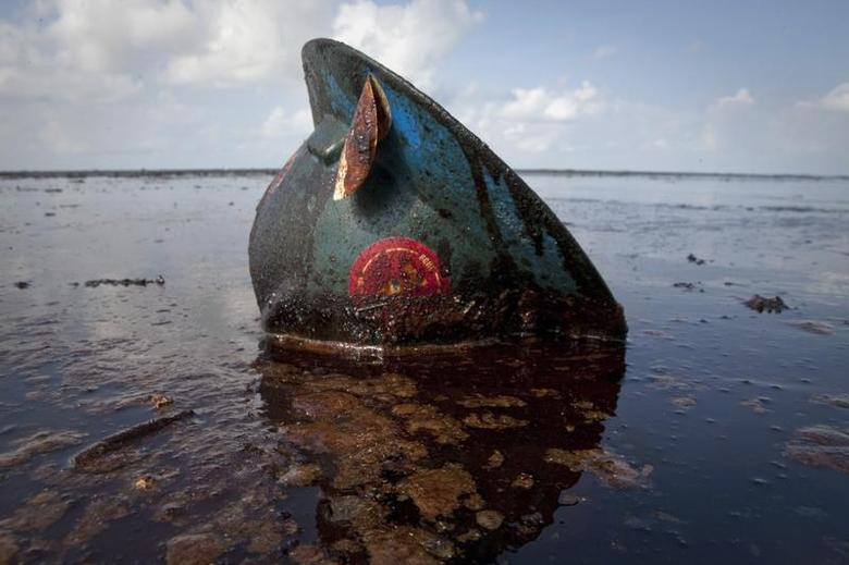 A hard hat from an oil worker lies in oil from the Deepwater Horizon oil spill on East Grand Terre Island, Louisiana June 8, 2010. REUTERS/Lee Celano