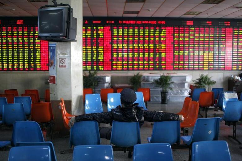 An investor sits in front of an electronic board showing stock information at a brokerage house in Shanghai, January 2, 2014. REUTERS/Aly Song