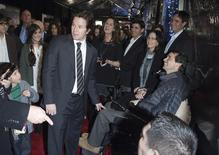 """Cast member Mark Wahlberg (L) greets a man in a wheelchair during the premiere of the movie """"Lone Survivor"""" in New York December 3, 2013. REUTERS/Carlo Allegri"""