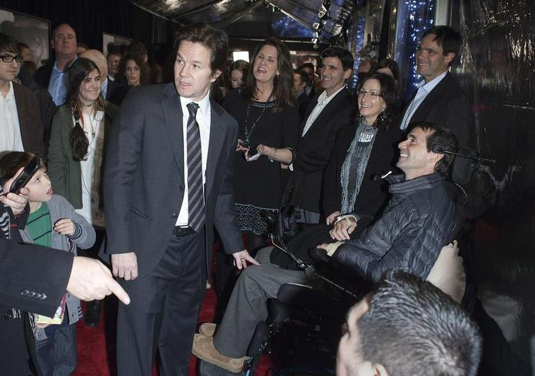 Cast member Mark Wahlberg (L) greets a man in a wheelchair during the premiere of the movie ''Lone Survivor'' in New York December 3, 2013. REUTERS/Carlo Allegri
