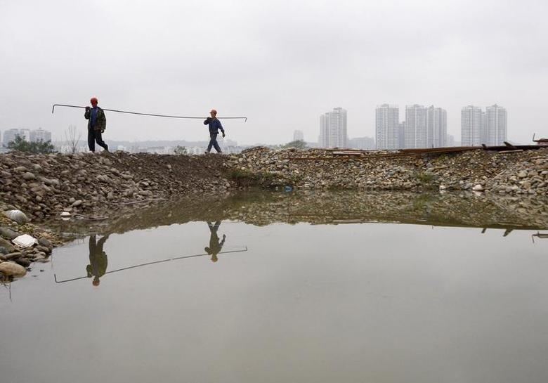 Labourers carry a steel bar at a construction site of a wetland park in Suining, Sichuan province October 14, 2009. REUTERS/Stringer