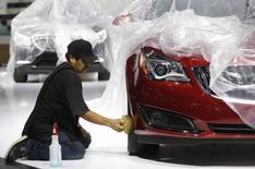 Préparatifs en vue de l'ouverture ce lundi du salon automobile de Detroit. Malgré un ralentissement attendu aux Etats-Unis après les années de rebond d'après-récession, les constructeurs automobiles apparaissent relativement optimistes concernant les ventes automobiles pour 2014. /Photo prise le 11 janvier 2014/REUTERS/Rebecca Cook