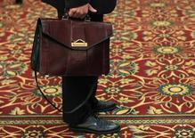 A man holds his briefcase while waiting in line during a job fair in Melville, New York July 19, 2012. REUTERS/Shannon Stapleton