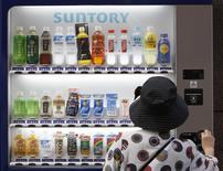 Una mujer adquiere un producto de una máquina expendedora de Suntory en Tokio, sep 10 2009. Suntory Holdings Ltd alcanzó un acuerdo por 16.000 millones de dólares para comprar a Beam Inc, lo que convierte a la compañía japonesa en el tercer fabricante de bebidas destiladas más grande del mundo y le da presencia global. REUTERS/Yuriko Nakao