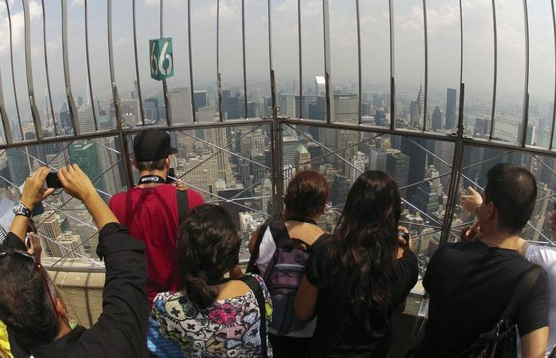 Visitors stand on the observation deck of the Empire State building in New York, August 3, 2012. REUTERS/Charles Platiau