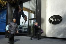 Pedestrians walk past the world headquarters of Pfizer in New York November 5, 2013. REUTERS/Adam Hunger