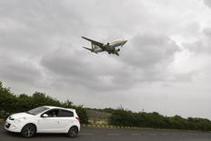 A car moves against the backdrop of a Jet Airways aircraft preparing to land at the airport in the western Indian city of Ahmedabad August 8, 2013. REUTERS/Amit Dave