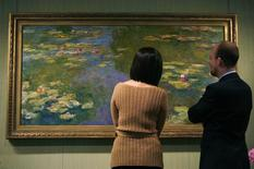 "Auction house Christie's employees examine Claude Monet's water-lily painting ""Le bassin aux nympheas"" in New York May 9, 2008. REUTERS/Brendan McDermid"