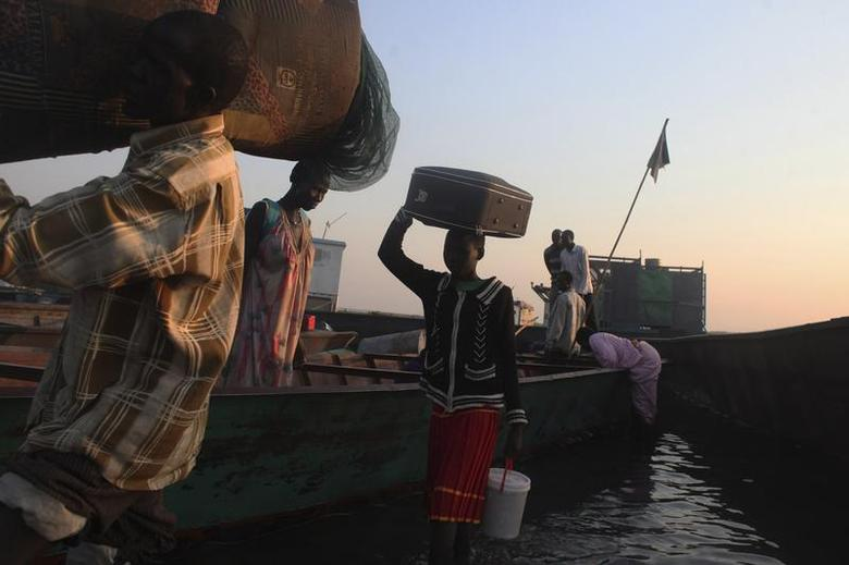 People displaced by the fighting in Bor county unload their belongings from a boat after arriving in the port of Minkaman, in Awerial county, Lakes state, in South Sudan, January 14, 2014. REUTERS/Andreea Campeanu