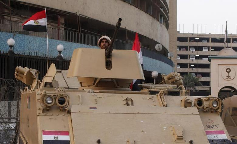 An Egyptian army soldier stands guard in front of the state television building in Cairo, July 9, 2013. REUTERS/Asmaa Waguih