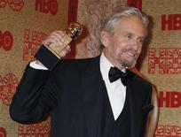 """Actor Michael Douglas holds the Golden Globe Award he won as Best Actor, Miniseries or Movie, for his role in HBO's """"Behind the Candelabra"""" at the HBO after party, after the 71st annual Golden Globe Awards in Beverly Hills, California January 12, 2014. REUTERS/Fred Prouser"""