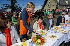 Crown Prince Willem-Alexander serves a meal to spectators during the annual Queens day in Veenendaal April 30, 2012. REUTERS/Frank van Beek/Pool
