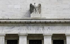 """Орёл на здании ФРС США в Вашингтоне 22 августа 2012 года. ФРС США следует быстро закрыть программу скупки облигаций, считают два """"ястреба"""" центробанка, обладающие правом голоса в 2014 году, при этом глава федерального резервного банка Далласа Ричард Фишер обещает использовать это право для поддержки сворачивания программы, даже если находящиеся в настоящий момент у рекордных высот акции начнут снижение. REUTERS/Larry Downing"""