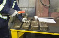 Сотрудник маркирует слитки золота на заводе при золотом руднике Кумтор в горах Тянь-Шаня 14 марта 2013 года. ВВП Киргизии в 2013 году вырос на 10,5 процента после снижения на 0,1 годом ранее, благодаря росту добычи золота на ключевом предприятии - золотом руднике Кумтор, спор о контроле над которым канадская Centerra Gold Inc ведёт с Бишкеком. REUTERS/Shamil Zhumatov