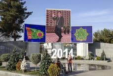 Люди прогуливаются на фоне экранов, показывающий президента Туркмении Курбанкули Бердымухамедова и национальных символов в Ашхабаде 13 декабря 2013 года. Туркмения увеличила сбор хлопка-сырца в 2013 году до 1,26 миллиона тонн с 1,235 миллиона годом ранее и готовится собрать около 1,2 миллиона тонн в этом году, сообщил в среду чиновник правительства. REUTERS/Stringer