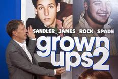 """Director Dennis Dugan gestures to the poster in the backdrop as he arrives for the premiere of the film """"Grown Ups 2"""" in New York, July 10, 2013. REUTERS/Lucas Jackson"""