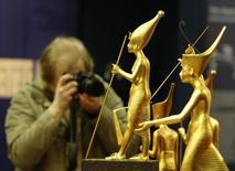 """Человек фотографирует фигурки фараона Тутанхамона во время мероприятия для прессы перед открытием выставки """"Тутанхамон: его могила и сокровища"""" в Мюнхене 8 апреля 2009 года. Археологи в Египте полагают, что обнаружили останки ранее неизвестного фараона, правившего более 3.600 лет назад. REUTERS/Michaela Rehle"""