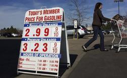 Consumidora passa por uma placa com preços de combustível em Westminster, Colorado. Os preços ao consumidor nos Estados Unidos registraram o maior aumento em seis meses em dezembro em meio à recuperação dos custos da gasolina, mas há poucos sinais de retomada mais ampla nos preços. 13/11/2013 REUTERS/Rick Wilking