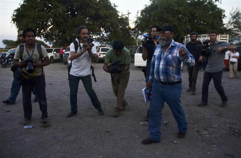 Estanislao Beltran (front R), spokesperson for the vigilantes, walks past photographers and camera operators in Tecapaltepec January 15, 2014. Vigilantes have been battling the Knights Templar cartel in the western state of Michoacan for almost a year, creating a major security problem for President Enrique Pena Nieto. REUTERS/Alan Ortega