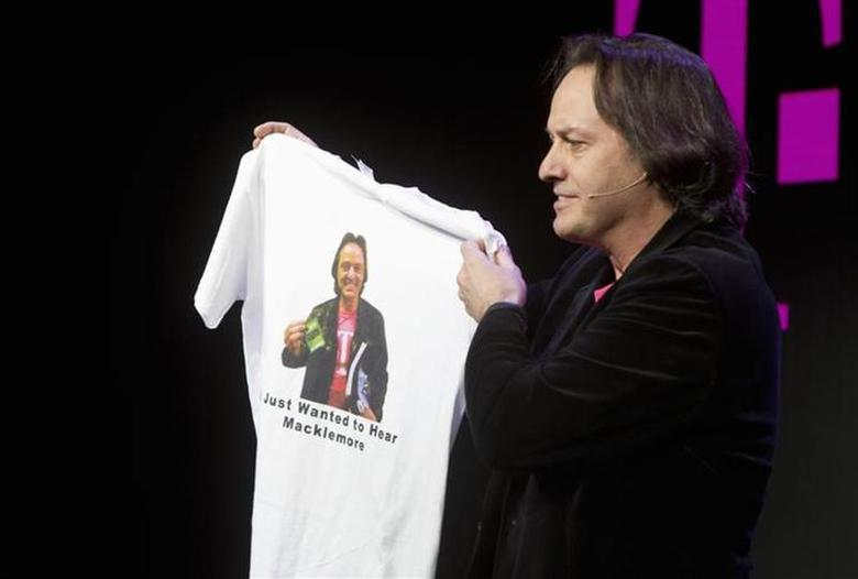 T-Mobile CEO John Legere holds a custom-made T-shirt with his image during a news conference at the 2014 International Consumer Electronics Show (CES) in Las Vegas, Nevada, January 8, 2014. REUTERS/Steve Marcus