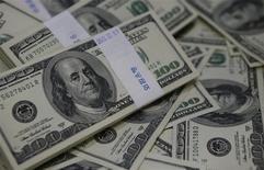 Foto de archivo de fajos de billetes de 100 dólares en un banco en Seúl. Ago 2, 2013. El dólar recortó el jueves parte de las pérdidas que sufrió previamente en la sesión, presionado por datos que mostraron un aumento en la cantidad de personas que reciben subsidios por desempleo regularmente en Estados Unidos, mientras que el dólar australiano cayó a mínimos no vistos en más de tres años. REUTERS/Kim Hong-Ji