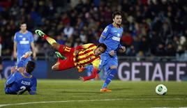 Barcelona's Neymar (C) falls as he is tackled by Getafe's Alexis Ruano (L) during their Spanish King's Cup soccer match at Colisseum Alfonso Perez stadium in Getafe January 16, 2014. REUTERS/Sergio Perez