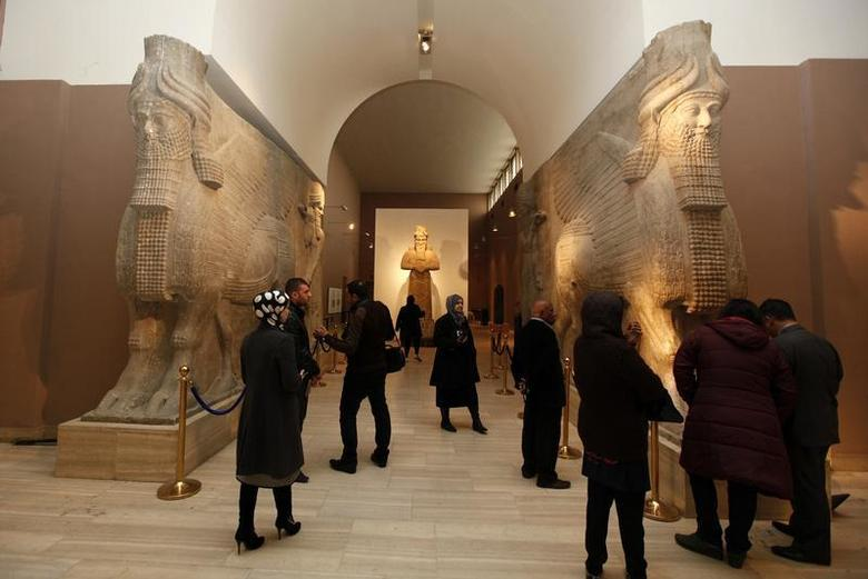 People look at ancient Assyrian human-headed winged bull statues at the Iraqi National Museum in Baghdad December 31, 2013. Baghdad is set to fully reopen its treasured National Museum, home to priceless artefacts plundered in the unchecked chaos following the 2003 U.S.-led invasion of Iraq. Picture taken December 31, 2013. REUTERS/Ahmed Saad