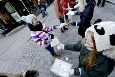 """People pass books by hand from the historic National Library of Latvia to the new building during """"Chain of booklovers"""" in Riga January18, 2014. REUTERS/Ints Kalnins"""