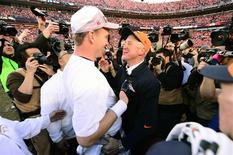 Denver Broncos quarterback Peyton Manning (18) and head coach John Fox celebrate the 26-16 victory against the New England Patriots following the 2013 AFC Championship football game at Sports Authority Field at Mile High. Ron Chenoy-USA TODAY Sports