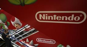 """Мужчина проезжает мимо рекламы Nintendo в магазине в Токио 20 января 2014 года. Акции Nintendo Co Ltd упали почти на 20 процентов в понедельник после того, как компания предупредила, что может третий год кряду закончить с операционным убытком, усилив разговоры о том, что компании-создателю легендарного """"Super Mario"""" пора задуматься над проводимой политикой. REUTERS/Yuya Shino"""