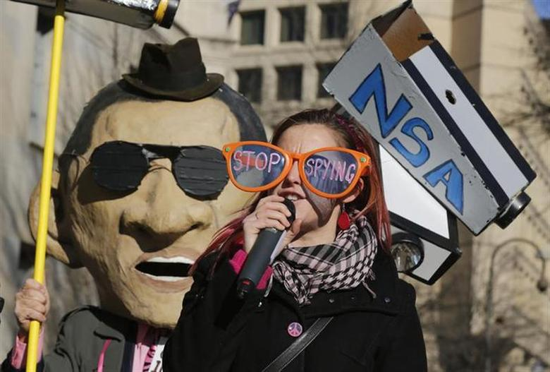 Member of the protest group, Code Pink, Alli McCracken, protests against U.S. President Barack Obama and the NSA before his arrival at the Department of Justice in Washington, January 17, 2014. REUTERS/Larry Downing