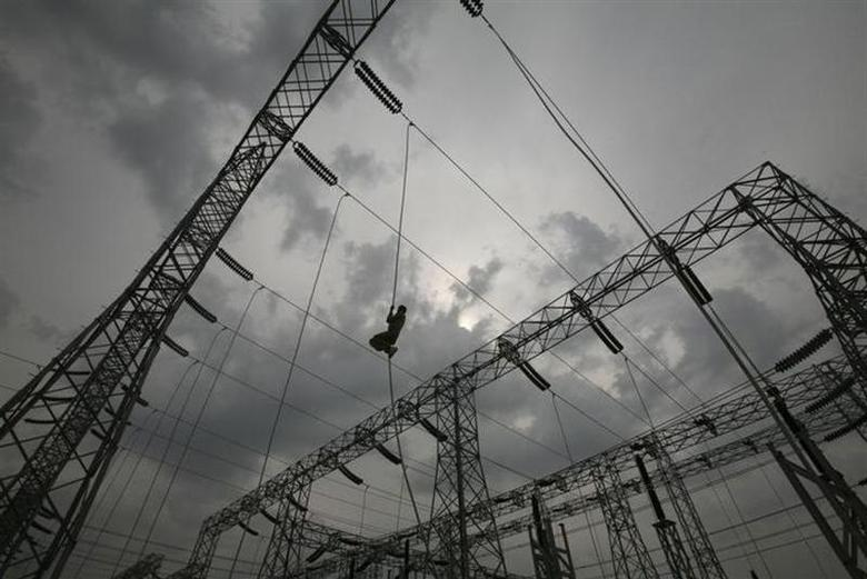 A worker installs an electric power cable on a pylon at a newly constructed power station in Jammu February 5, 2011. REUTERS/Mukesh Gupta/Files