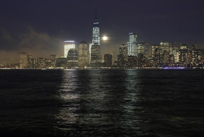 A full moon rises behind the skyline of Lower Manhattan and One World Trade Center in New York, January 15, 2014. REUTERS/Gary Hershorn