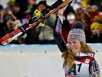 Mikaela Shiffrin from the U.S. celebrates with the trophy after winning the World Cup women's slalom race in Flachau January 14, 2014. REUTERS/Dominic Ebenbichler