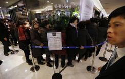 An apology (C) to customers is displayed as customers wait in a line to apply for their credit cards to be reissued at Lotte Card's main office in Seoul January 21, 2014. REUTERS/Kim Hong-Ji